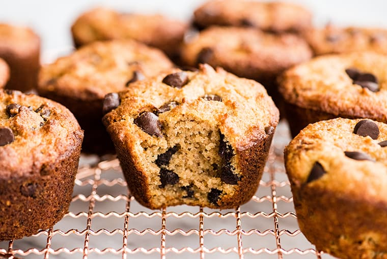 Front view of nine healthy chocolate chip muffins on a cooling rack, the front center muffin has a bite taken out of it