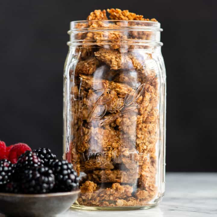 front view of a glass jar filled with peanut butter granola