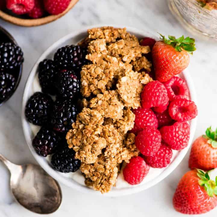 overhead view of a bowl of yogurt topped with berries and a lot of Peanut Butter Granola