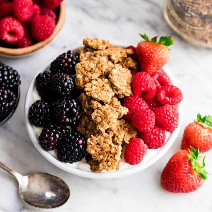 front view of a bowl of yogurt topped with berries and homemade peanut butter granola
