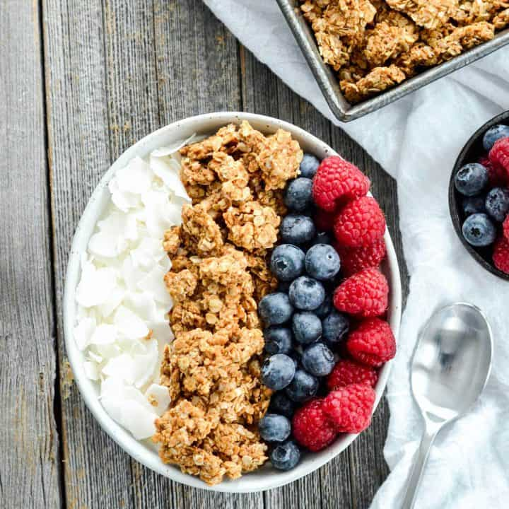 overhead view of peanut butter granola in a bowl with berries and coconut