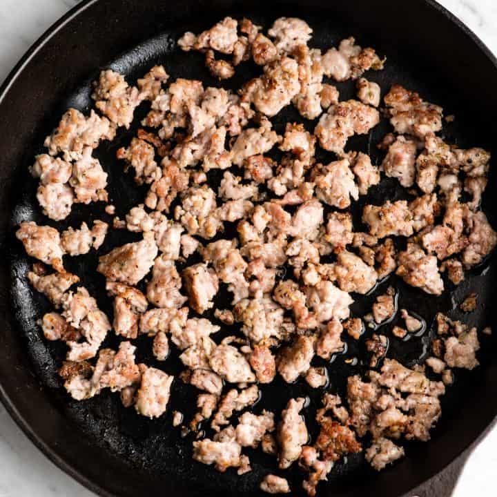 overhead view of sausage browning in a cast iron skillet.