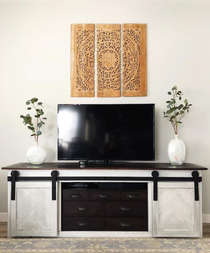 front view of a farmhouse entertainment center with faux eucalyptus plans in vases on either side of the TV.