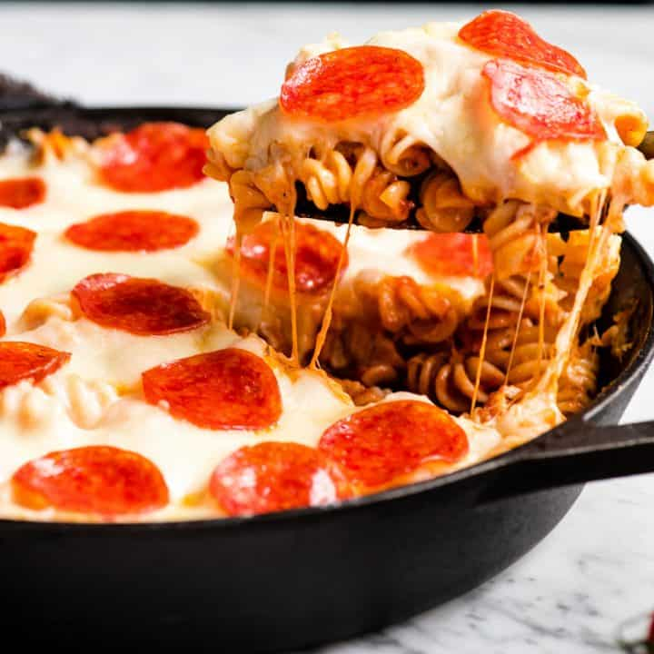 front view of a piece of pizza casserole being pulled from the pan as strings of cheese pull off too
