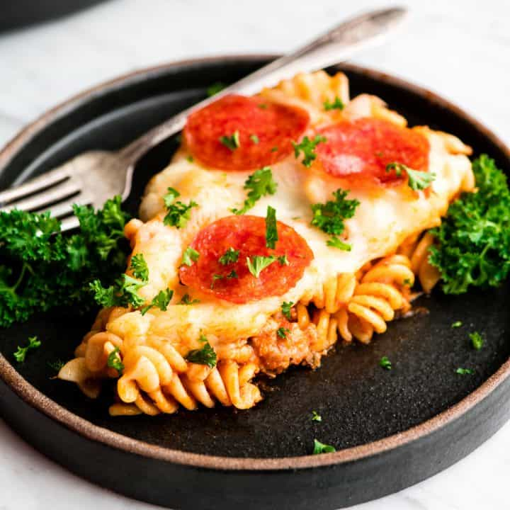front view of a serving of pizza casserole on a plate sprinkled with parsley