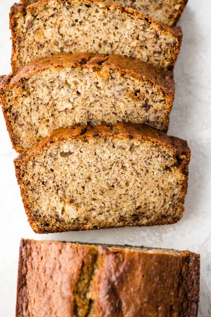 Overhead view of a loaf of banana bread with three slices cut out of it laying flat on a plate