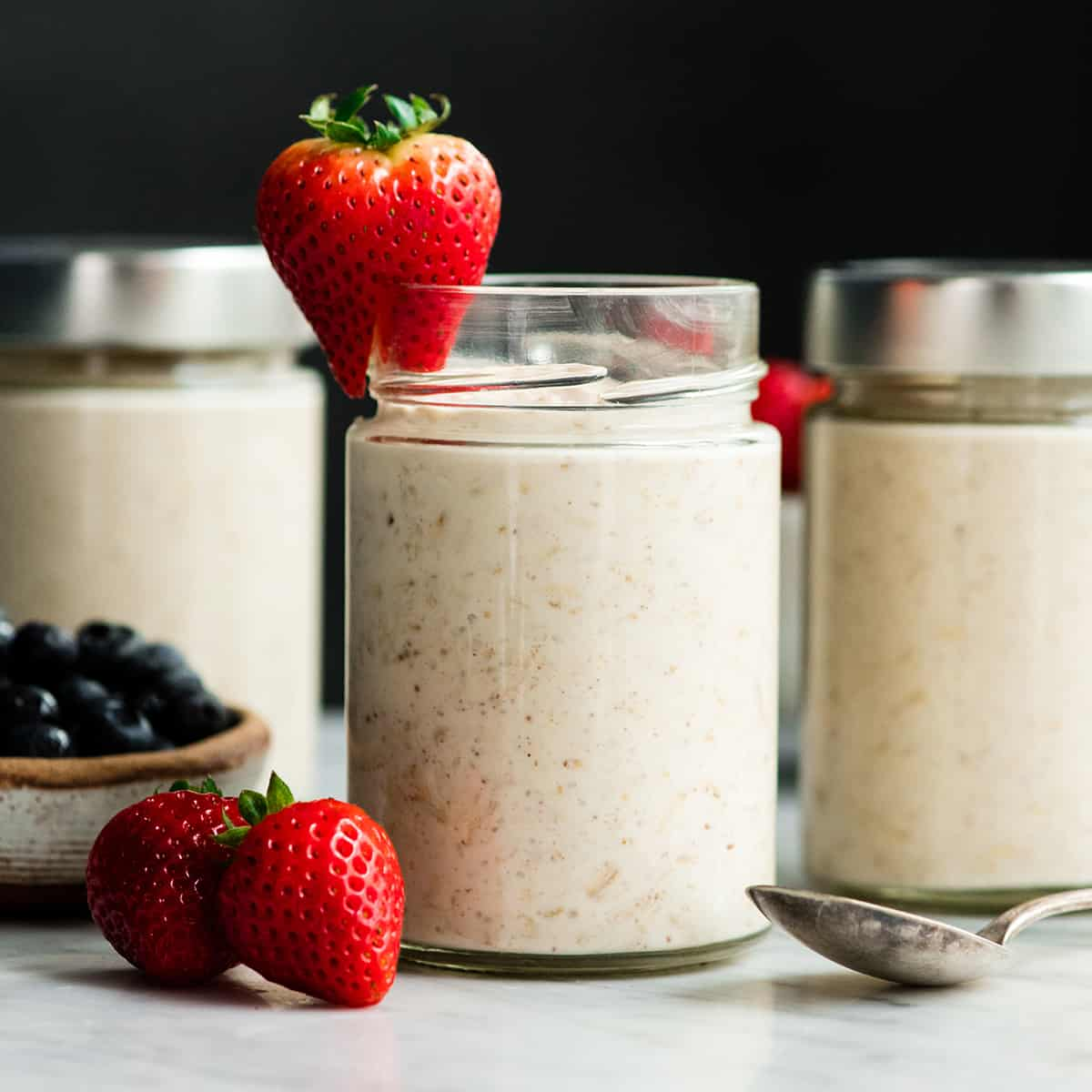 front view of three glass jars of Yogurt Overnight Oats with berries on top and around them