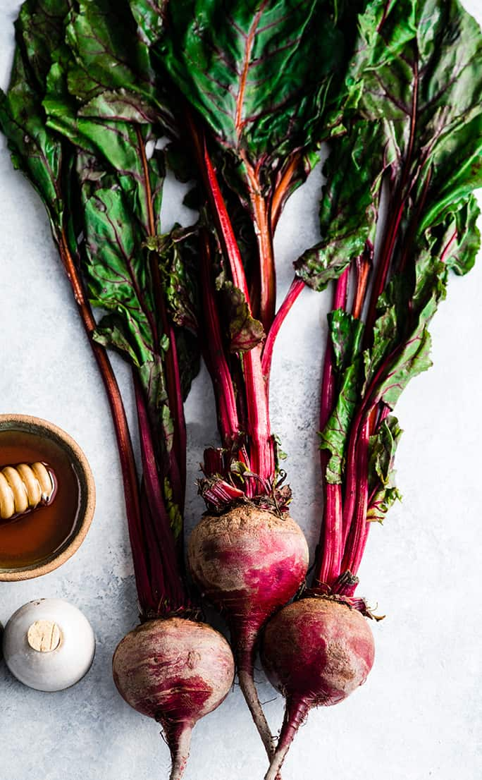 Overhead view of three fresh beets with the greens and stems still attached before peeling or cutting to be used in this roasted beet recipe