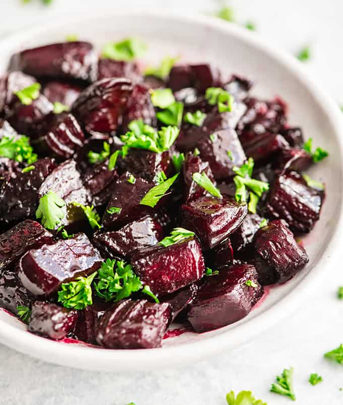 up close overhead view of balsamic roasted beets in a bowl garnished with chopped beet greens