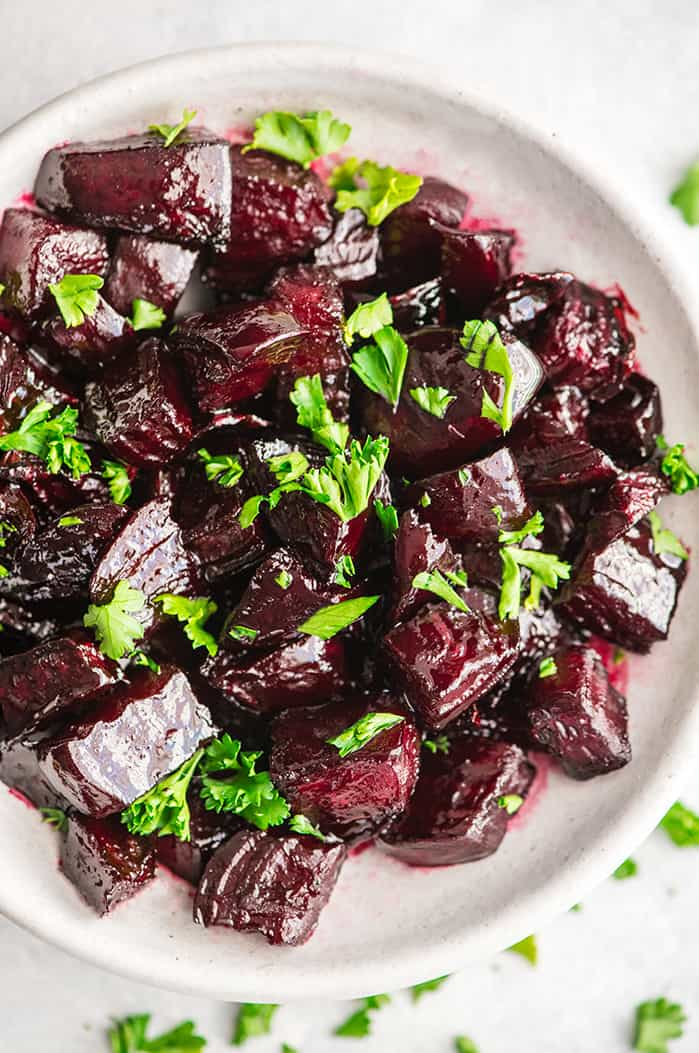 Overhead view of a bowl of balsamic roasted beets garnished with beet greens
