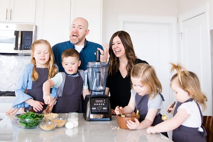 Front view of a mom and dad and their four kids cooking with kids