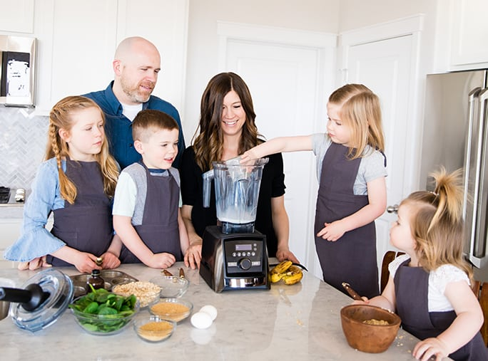 Front view of a mom and dad and their four kids adding ingredients to a blender while they're Cooking with Kids