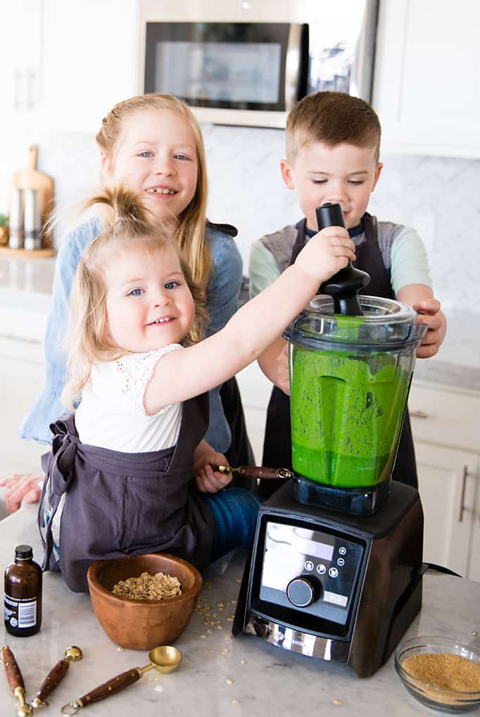front view of three kids blending in a blender in this article about Front view of a mom and her four kids blending in a blender while she's Cooking with Kids