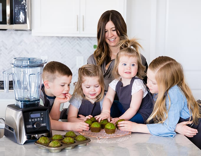 front view of a mom and her five kids reaching for muffins they made together while she was Front view of a mom and her four kids blending in a blender while she's Cooking with Kids