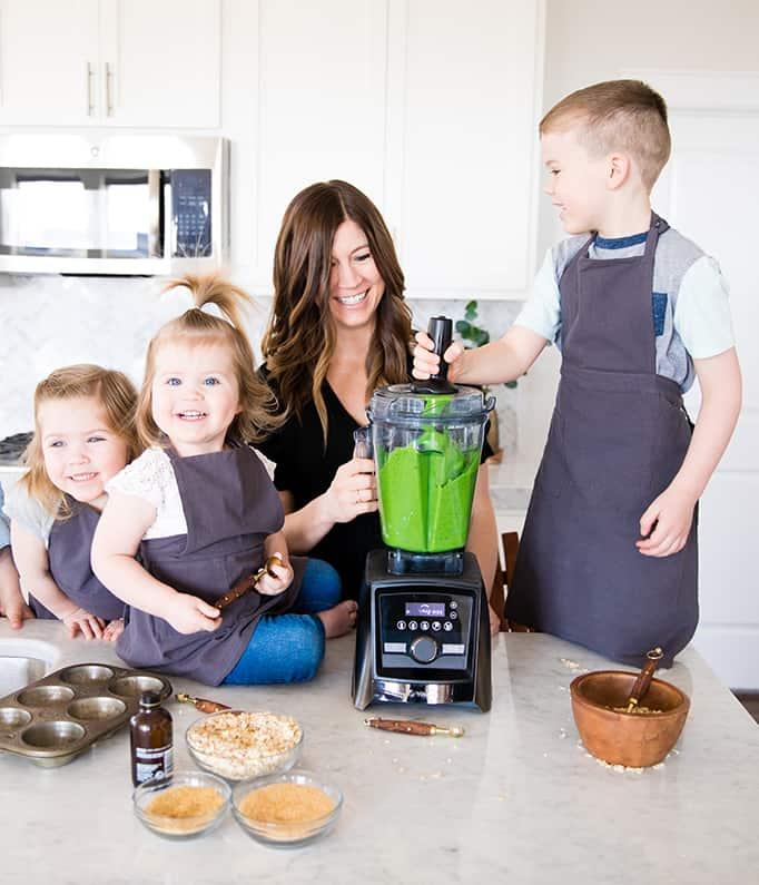Front view of a mom and her four kids blending in a blender while she's Cooking with Kids