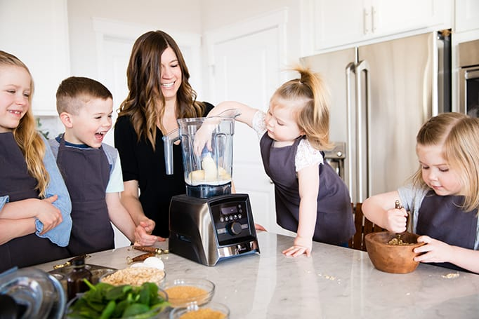 Front view of a mom and her four kids, the littlest one adding a banana to the blender while she's Cooking with Kids