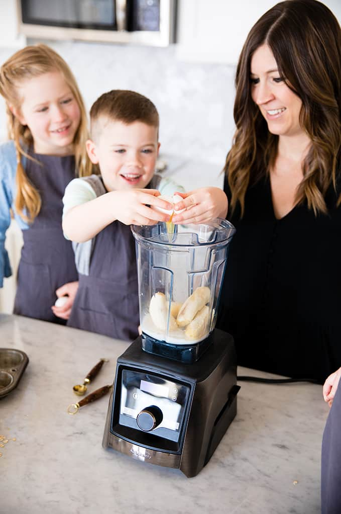 front view of a boy cracking an egg into a blender while his mom and sister watch in this article about Front view of a mom and her four kids blending in a blender while she's Cooking with Kids