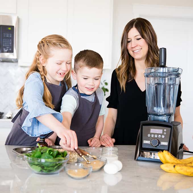 Front view of a mom and her two kids measuring ingredients while she's cooking with kids