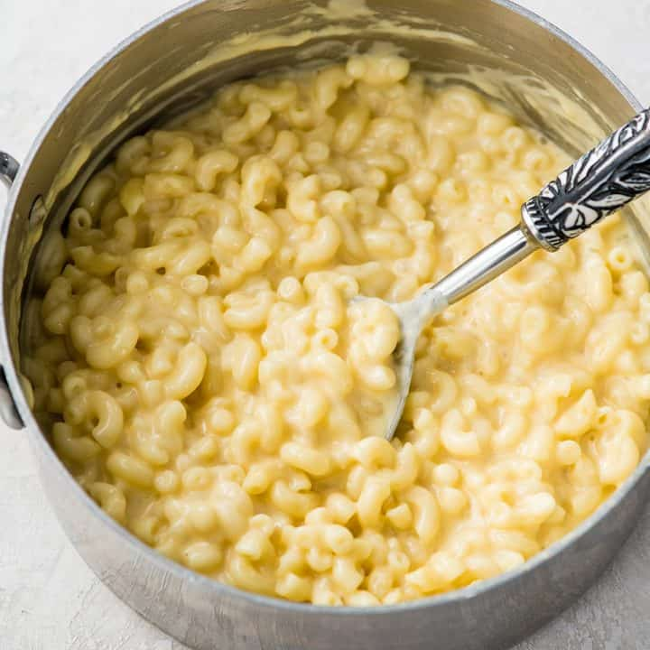 a spoon taking a scoop of homemade mac and cheese out of a saucepan