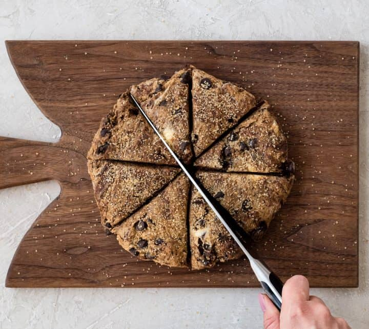 Overhead view of a hand using a large knife to cut this Mocha Chocolate Scones recipe into eight scones