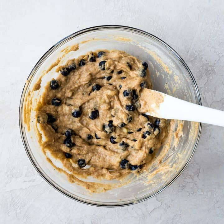 how to make paleo blueberry  muffins blueberries being mixed into the paleo blueberry muffin batter with a white spatula
