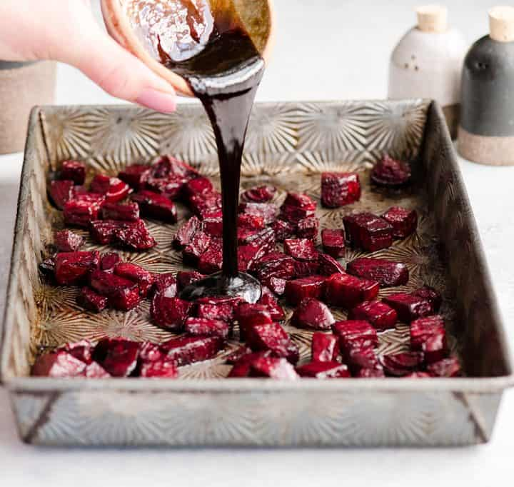 photo showing How to Roast Beets pouring balsamic vinegar on the partially roasted beets in a pan