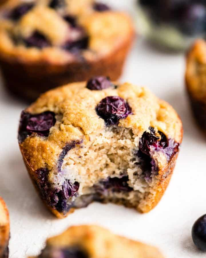 a paleo blueberry muffin with a bite taken out of it surrounded by other muffins & berries