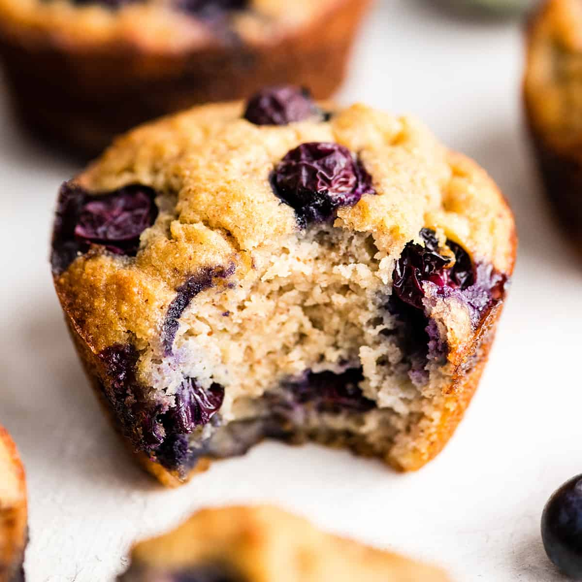 up close photo of a paleo blueberry muffin with a bite taken out of it
