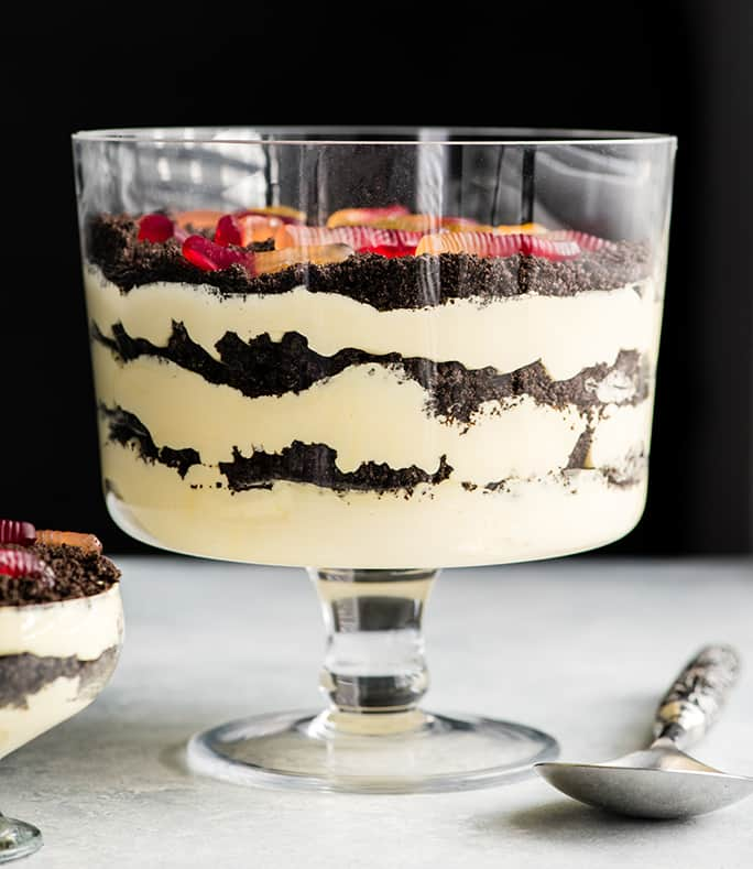 Front view of this Oreo Dirt Cake Recipe in a glass trifle dish with three layers of pudding and three layers of crushed Oreos with gummy worms on top and a spoon and a single-serve dish of Oreo Dirt Cake next to it