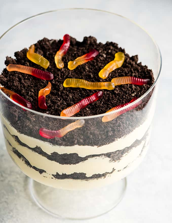 Front view of this Oreo Dirt Cake Recipe in a glass trifle dish with three layers of pudding and three layers of crushed Oreos with gummy worms on top