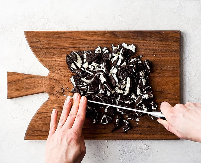 Overhead view of a two hands cutting Oreos with a knife on a rectangular wooden cutting board