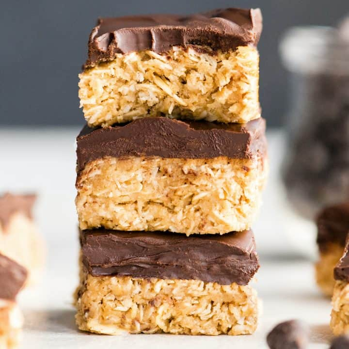 front view of a stack of three No-Bake Oatmeal Bars with Peanut Butter & Coconut, the top one has a bite taken out of it