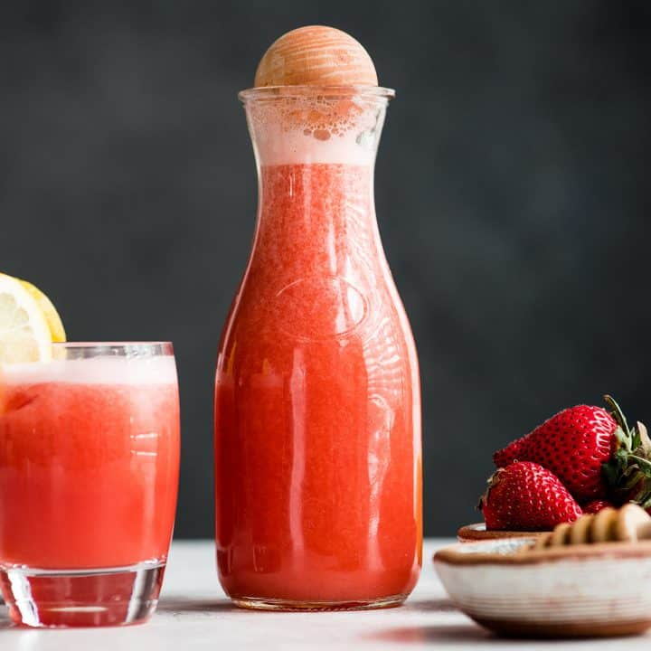 front view of a glass pitcher of Homemade Strawberry Lemonade and a glass of Homemade Strawberry Lemonade and a bowl of strawberries next to it