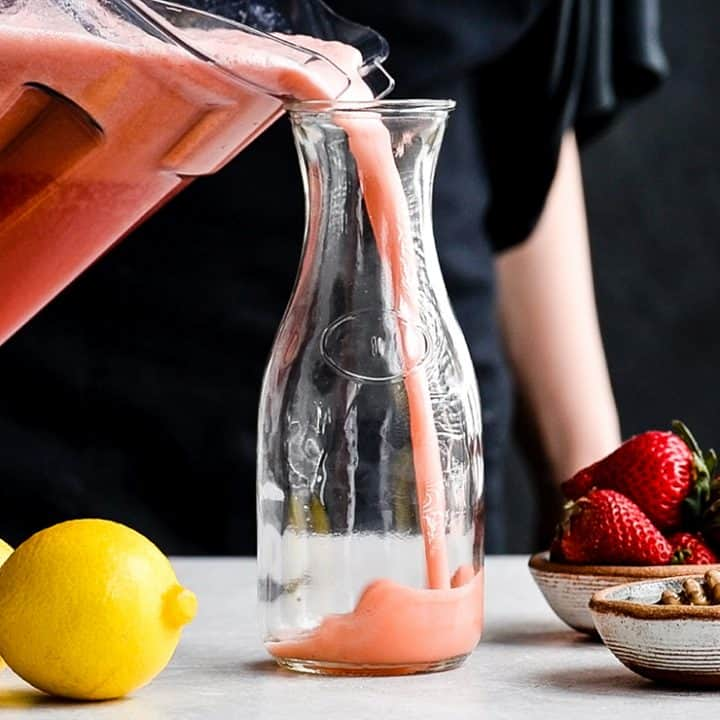 front view of a woman pouring Homemade Strawberry Lemonade from the vitamix container into a glass pitcher.