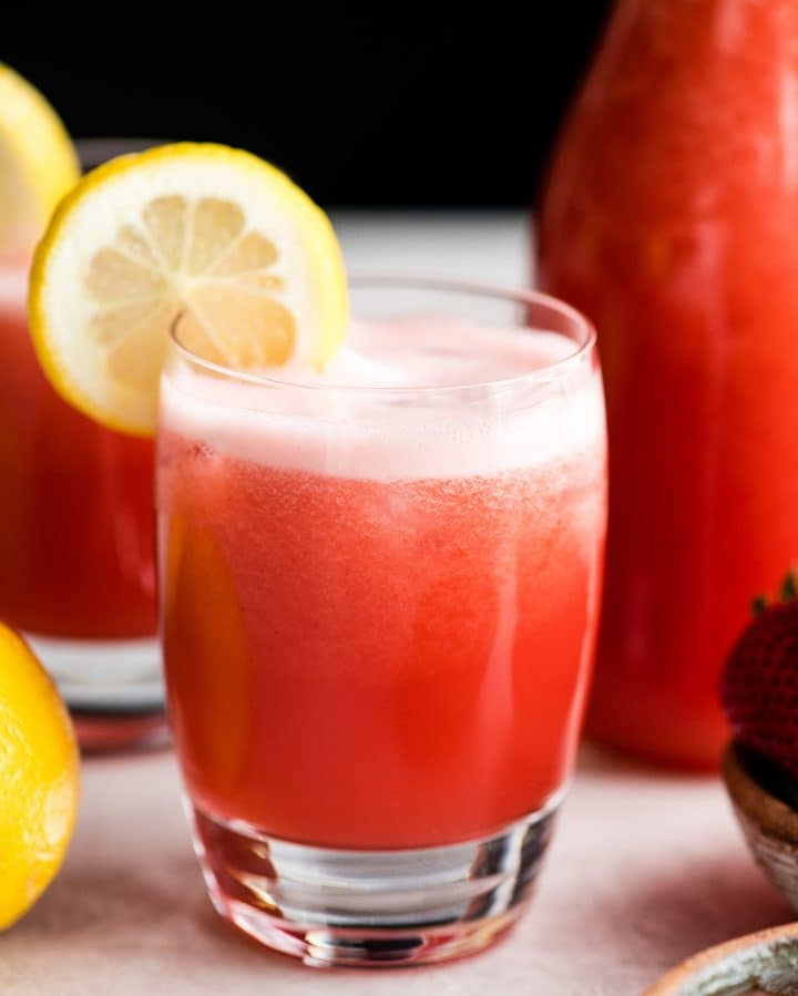 front view of a glass of Homemade Strawberry Lemonade with a lemon slice on the rim of the glass