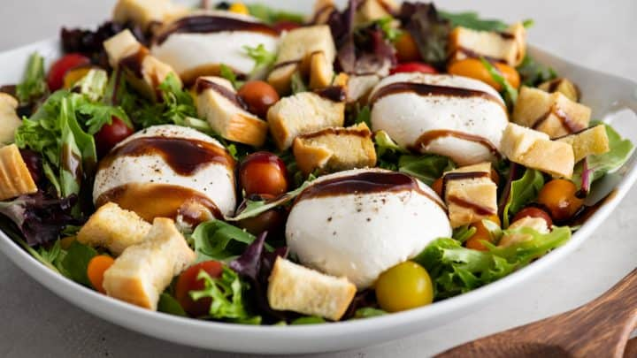 front view of burrata salad after dressing has been put on