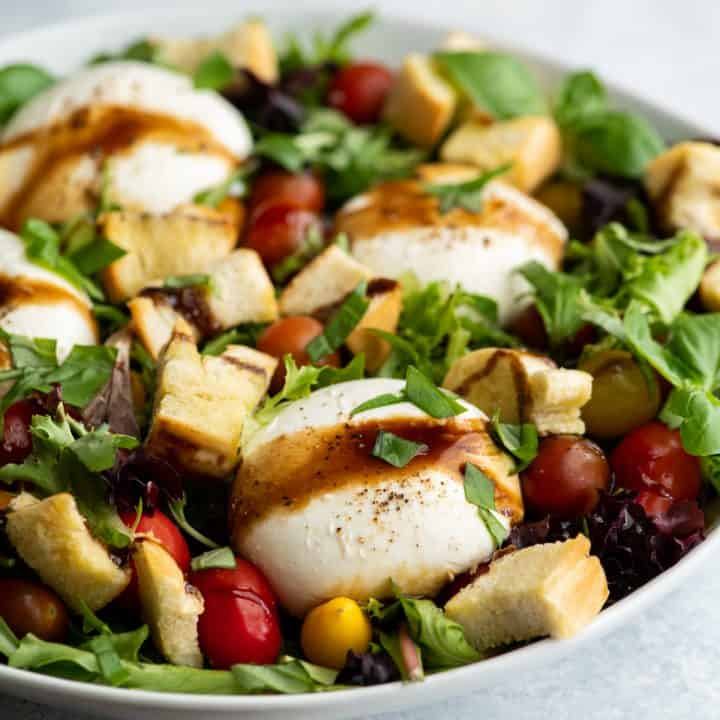 burrata salad in a large white serving dish drizzled with balsamic vinaigrette