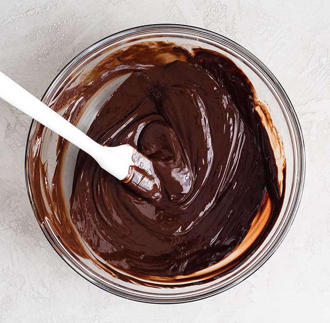 Overhead view of melted chocolate butter mixture in a glass bowl with a white spatula in it to make the Brownie Recipe