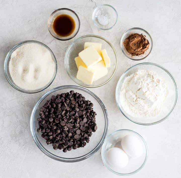 overhead view of the 8 ingredients used to make this brownie recipe in glass bowls.