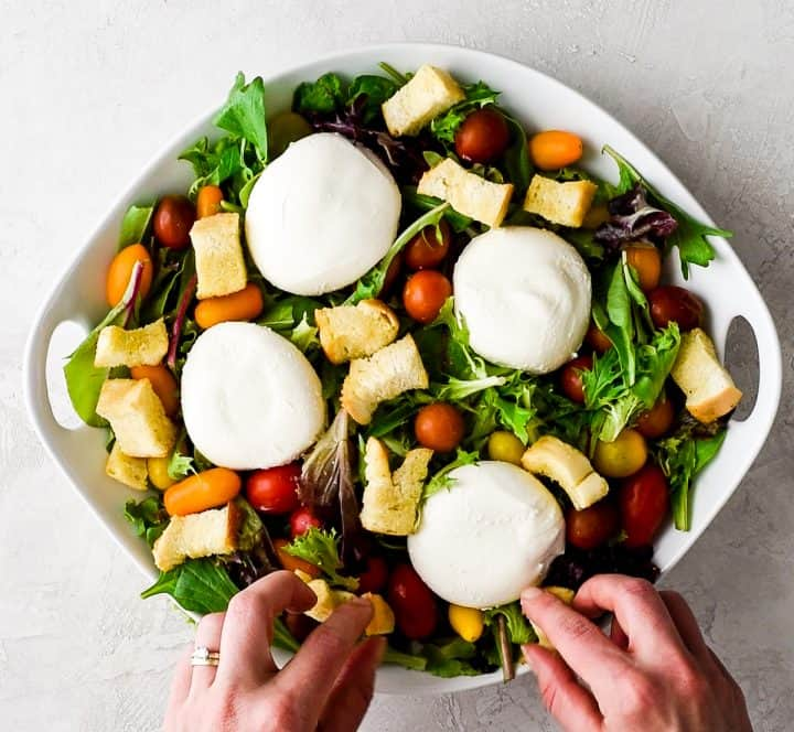 overhead view of a large white bowl with spring mix, baby tomatoes, four burrata cheese rounds and hands putting croutons on top of the greens making this burrata salad