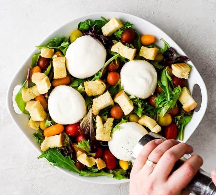 overhead view of hands grinding pepper on the top of a burrata cheese round that's on a large white bowl with spring mix, baby tomatoes, four burrata cheese rounds and homemade croutons - a burrata salad