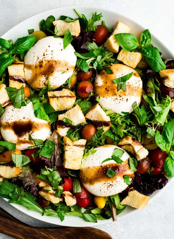 overhead view of a burrata salad in a large white serving dish drizzled with balsamic vinaigrette
