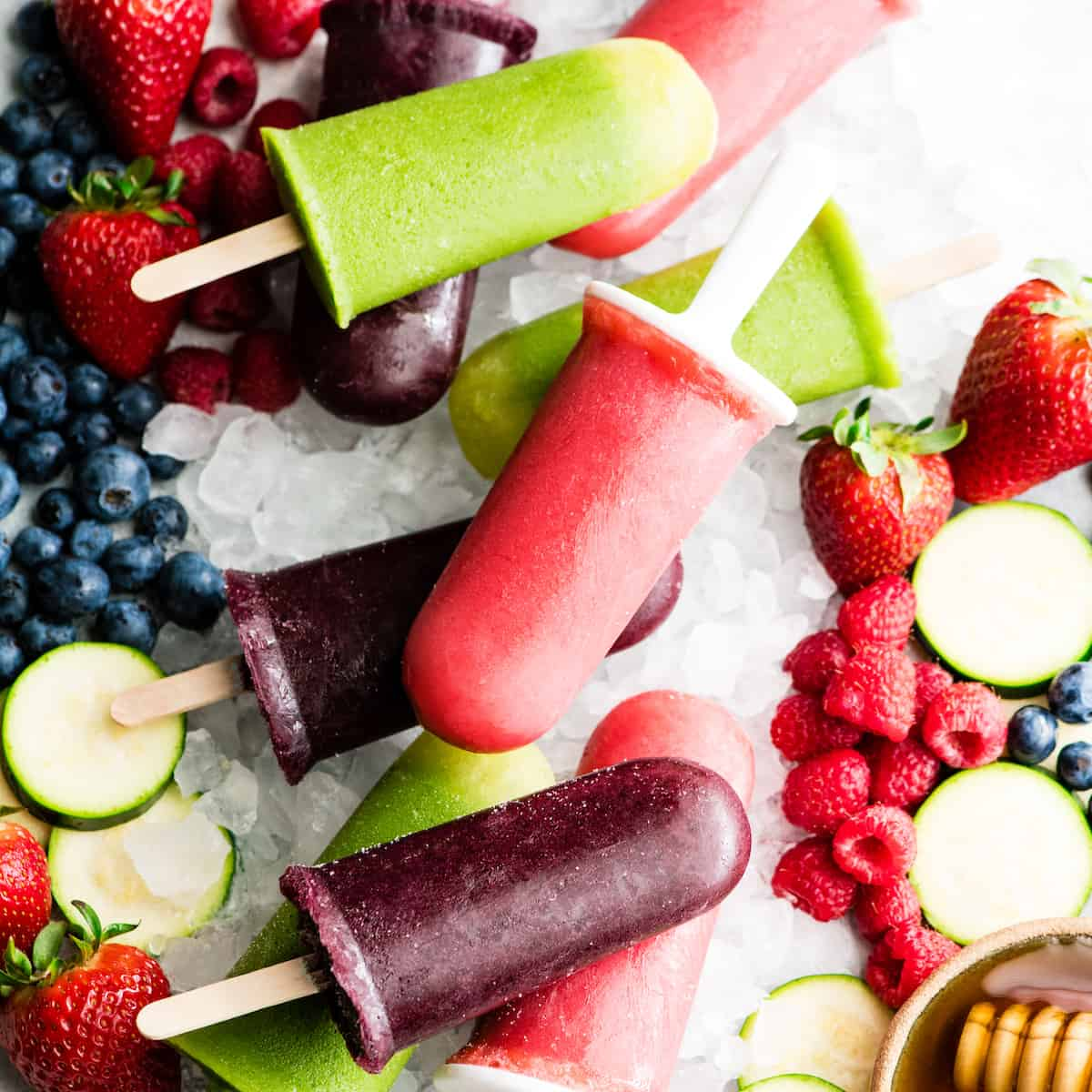 overhead view of 9 Homemade Fruit Popsicles in three colors: purple, green and red. Laying out on crushed ice with fresh fruit surrounding them.