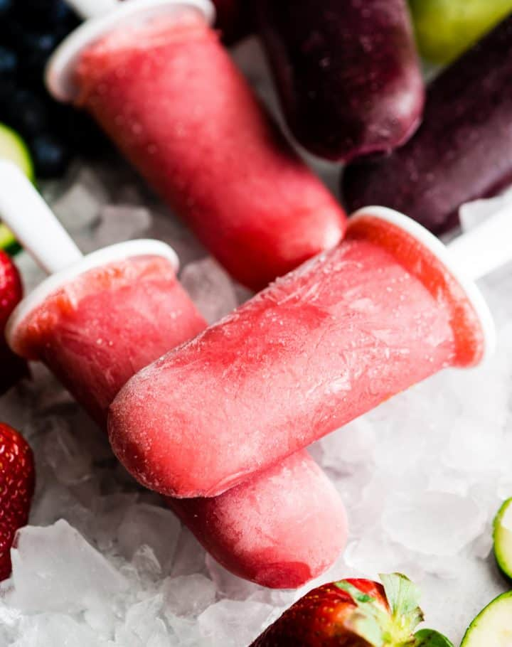 two red homemade popsicles sitting on top of each other over ice