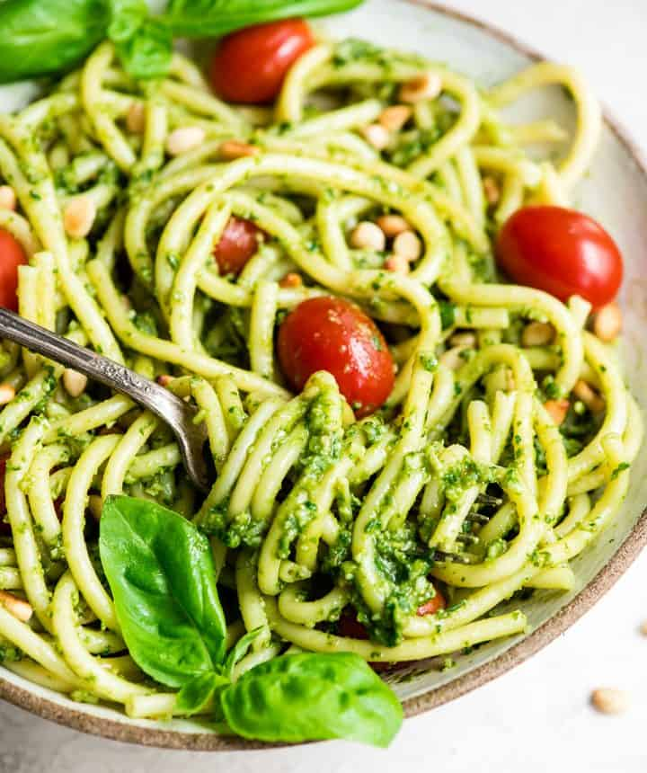 up close front view of a bowl of pasta with Basil Pesto Sauce on it garnished with fresh basil leaves, toasted pine nuts, and red cherry tomatoes. There is a fork with pasta twirled on it.