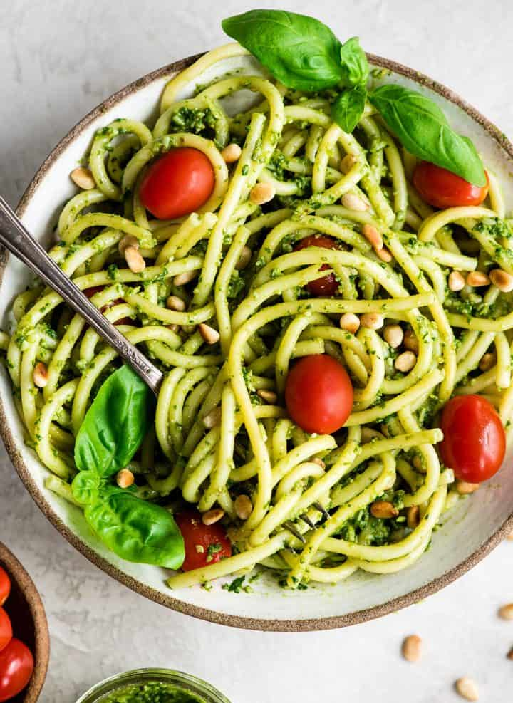 overhead view of a bowl of pasta with Basil Pesto Sauce on it garnished with fresh basil leaves, toasted pine nuts, and red cherry tomatoes. There is a fork with pasta twirled on it.