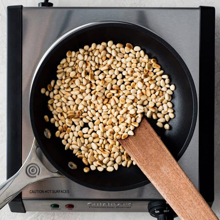 overhead view of pine nuts toasted in a small nonstick black fry pan on a cast iron burner being stirred with a wooden stirrer