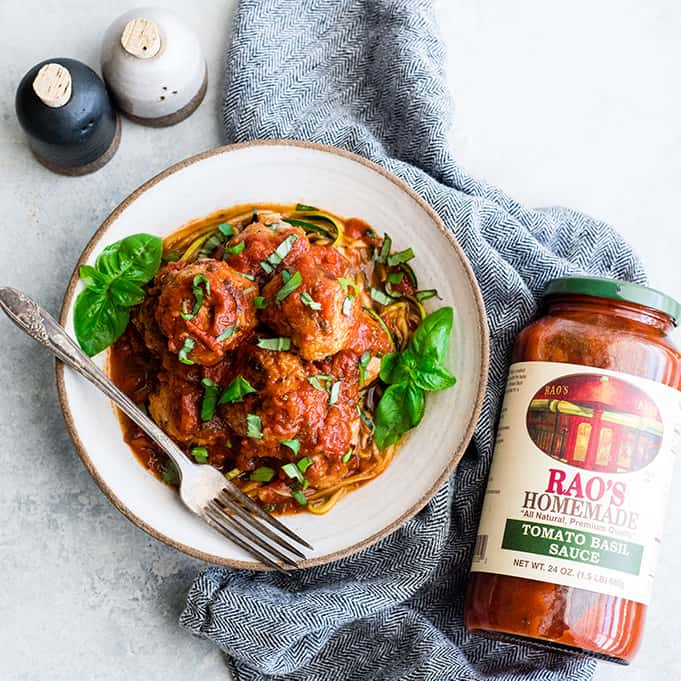 overhead view of a bowl of turkey meatballs in pasta sauce over a bed of zucchini noodles with a jar of rao's homemade sauce next to it