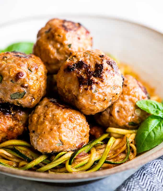 up close front view of six Healthy Turkey Meatballs in a bowl on top of zucchini noodles