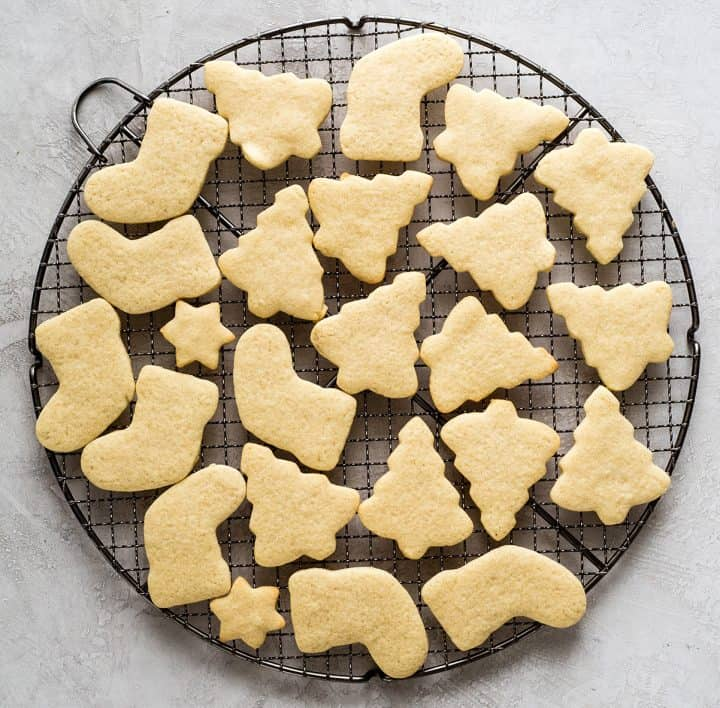 overhead photo of cut-out sugar cookies in Christmas shapes on a wire cooling rack